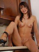 Seksowna brunetka rozbiera się w kuchni